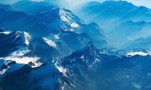 陽光下美麗的雪山山頂攝影圖片