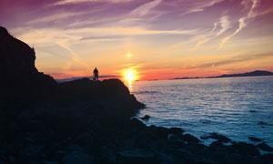 夕阳下的海边风景和人物剪影摄影图片