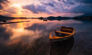 夕陽下停泊在湖邊的小舟攝影圖片