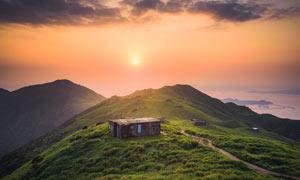 傍晚大山山顶上的小屋摄影图片