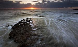 傍晚大海中的礁石攝影圖片