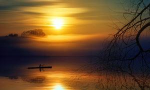 落日下湖中滑行的小舟摄影图片
