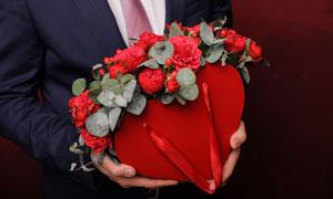 雙手捧著心形禮物盒的男人高清圖片