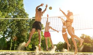 玩沙灘排球的帥哥美女攝影高清圖片