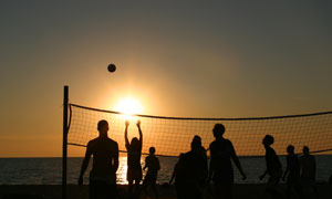 夕陽中打排球的一群人攝影高清圖片