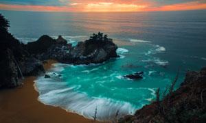 霞光下涌向海岸的潮水摄影高清图片