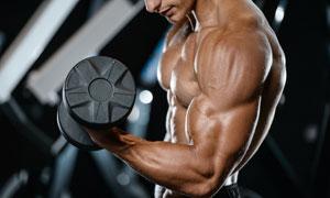 手握著啞鈴的肌肉男子攝影高清圖片