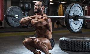 蹲姿扛杠鈴的健身男人攝影高清圖片