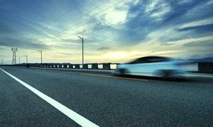 公路上疾馳的轎車風光攝影高清圖片