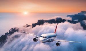 在云端之上飛行的飛機攝影高清圖片
