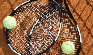 放在土地上的網球球拍攝影高清圖片
