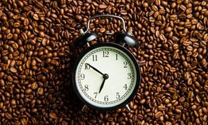 擺放在一堆咖啡豆山的鬧鐘高清圖片