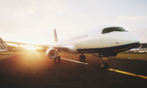 停在機場跑道上的飛機逆光攝影圖片