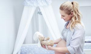 拿起玩具端詳的孕媽媽攝影高清圖片