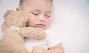 抱著玩具熊睡著的寶貝攝影高清圖片