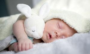 抱著安撫玩具入睡的小寶貝高清圖片