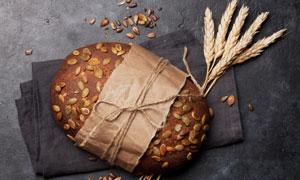 麥穗與一塊包好的面包攝影高清圖片