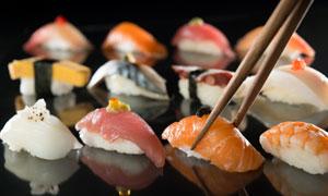 被筷子夾著的美味壽司攝影高清圖片