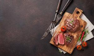 刀叉番茄與美味的牛排攝影高清圖片