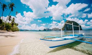 白云椰树群山与沙滩小船等高清图片