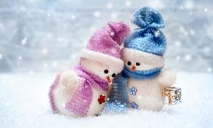 兩個雪地上的雪人布偶攝影高清圖片