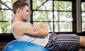 在做健身球運動的男子攝影高清圖片