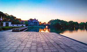 夕阳下的西湖湖边景观摄影图片