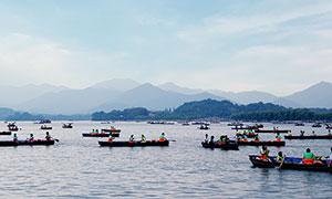 西湖上游客划着小舟摄影图片