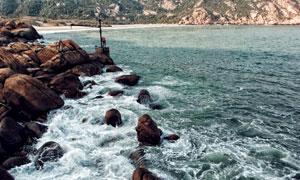 拍打着岸边礁石的海水摄影高清图片