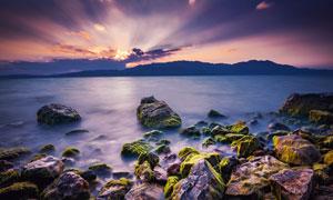 海边岩石与夕阳下远山摄影高清图片
