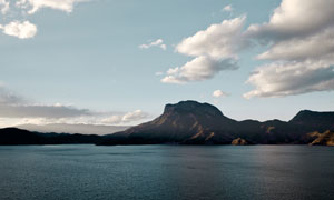 白色云朵下的山峦大海摄影高清图片