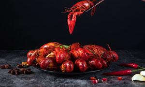 筷子夹起的美食小龙虾摄影图片
