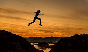 傍晚山顶上跨越的人物摄影图片
