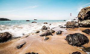 海边沙滩上的海浪和岩石摄影图片