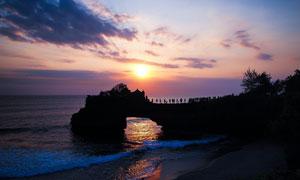 夕阳下的海边美景和游客摄影图片
