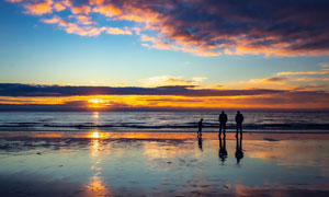 夕阳下的沙滩和人物剪影摄影图片