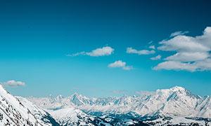 蓝天白云下的雪山山顶美景摄影图片