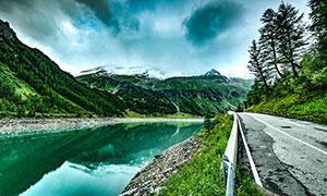 乌云喜爱的山间道路和湖泊摄影图片