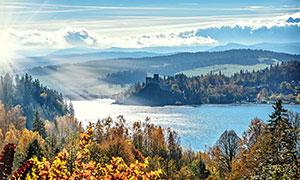 阳光下的山林和湖泊摄影图片