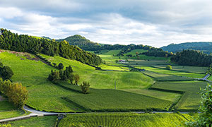 乌云下的农田和山林摄影图片