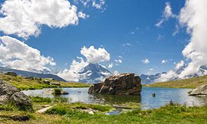 蓝天白云下的湖泊和石头摄影图片