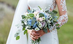 白色婚纱装扮新娘手中捧花摄影图片