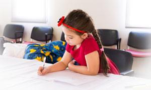 在教师里认真学习的小女孩摄影图片