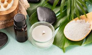 蠟燭浴鹽與鵝卵石綠葉特寫攝影圖片
