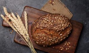 在砧板上的全麦面包与麦穗高清图片