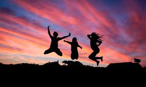 傍晚三个人跳起剪影摄影图片
