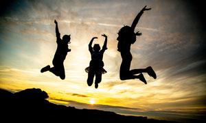傍晚跳跃起来的三个人剪影摄影图片