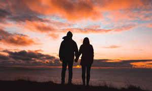 傍晚在海边看日落的情侣剪影摄影图片
