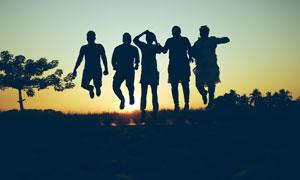 夕阳下跃起的人物剪影摄影图片