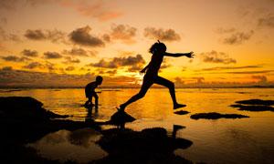 夕阳下海边玩耍的母子剪影摄影图片